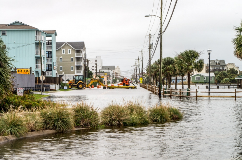 A project designed to dredge the Carolina Beach Lake will begin later this month. The Town hopes it will help improve stormwater runoff in the areas surrounding the lake that traditionally flood during intense storms. (Pictured above:) Heavy rainfall in October 2015 caused the lake to overflow into South Lake Park Blvd and other area streets.