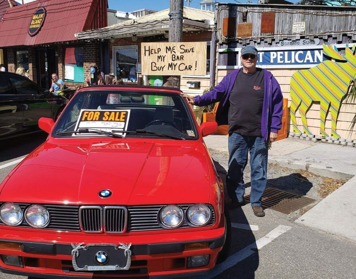 "Danny McLaughlin, owner of the Fat Pelican Bar in Carolina Beach posted a photo in recent days of his red BMW with a sign that read, ""Help me save my bar, buy my car!"". Danny said he's been struggling to pay the bills since bars were ordered to close during COVID-19. Recently  people helped by donating  $13,000 overnight online."