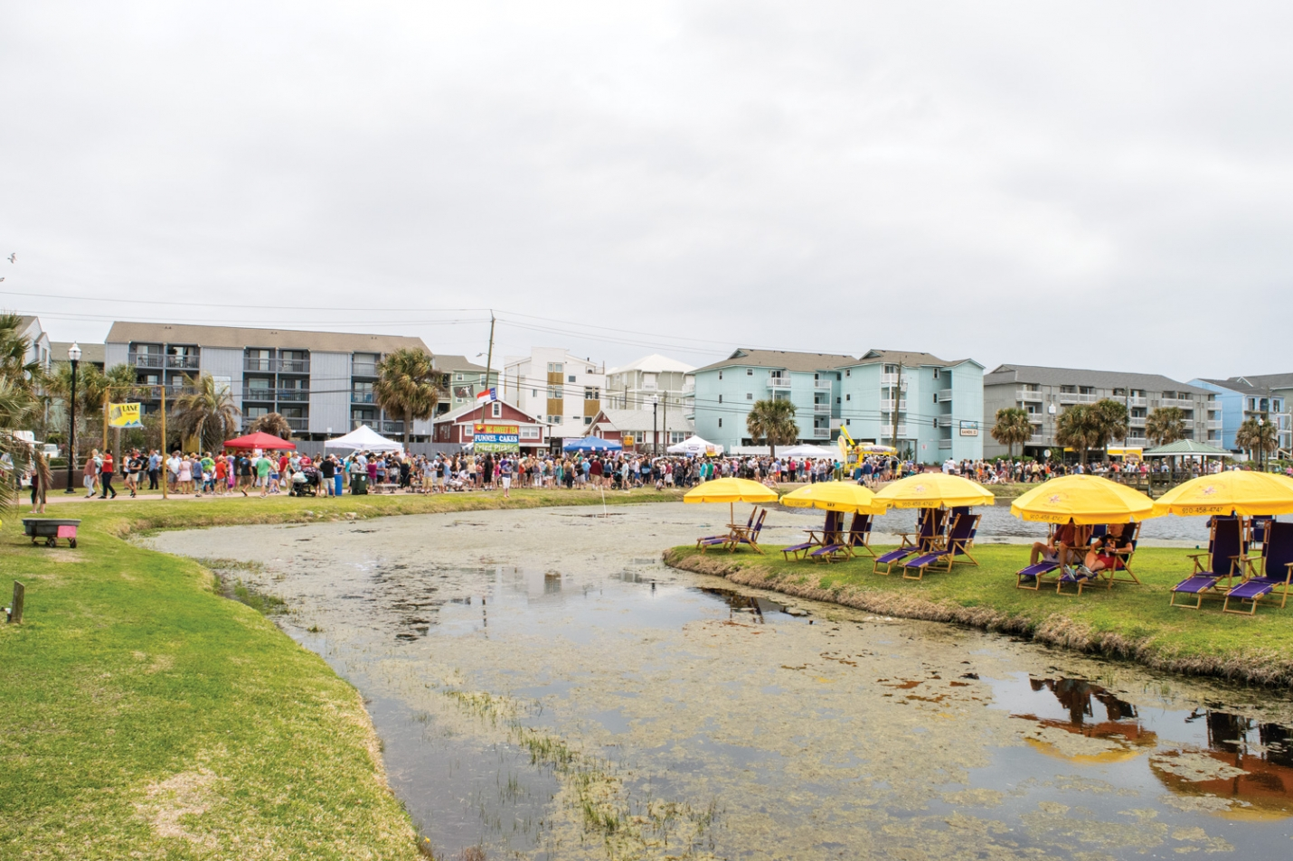 The Town of Carolina Beach is planning regular maintenance of the Carolina Beach Lake to remove algae and litter from the water. In recent weeks several residents have complained about the appearance of the algae and the foul smell with the arrival of warmer weather.  (Photo from festival held at the lake in April 2018.)