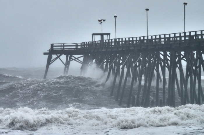(Photo from file: Hurricane Matthew caused beach erosion, power outages and fallen trees on October 8th and 9th, 2016 in the Cape Fear Region. Pictured above: Kure Beach Pier)