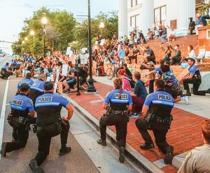 (Photo via Facebook: Katy Caffarél) : Wilmington Police officers taking a knee in front of protestors in downtown Wilmington on Monday afternoon. That followed a tense protest on Sunday night. The City of Wilmington, New Hanover County and area municipalities implemented curfews on Tuesday.