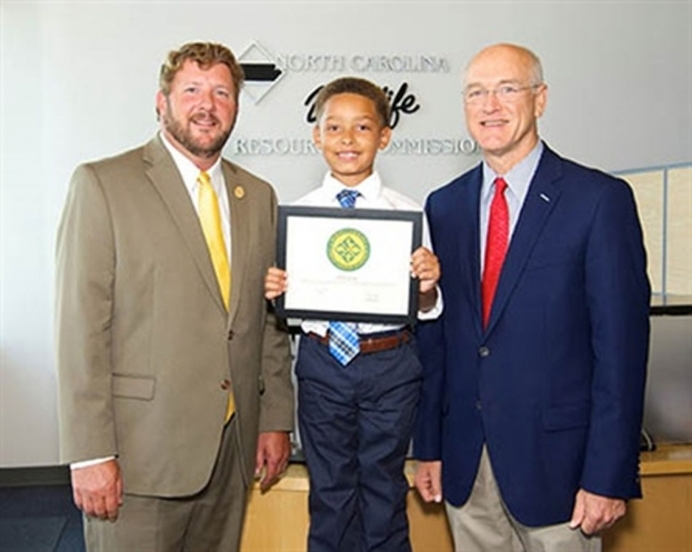 Brooks Grady, 7, of Grifton, accepts his lifetime unified sportsman license certificate from Wildlife Commission Chairman John Litton Clark (left) and license donor Russell Rhodes, from Neuse Sport Shop in Kinston.